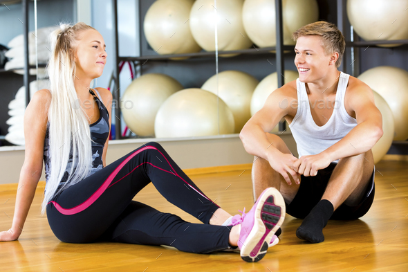 Smiling Young Man And Woman Sitting In Gym - Stock Photo - Images
