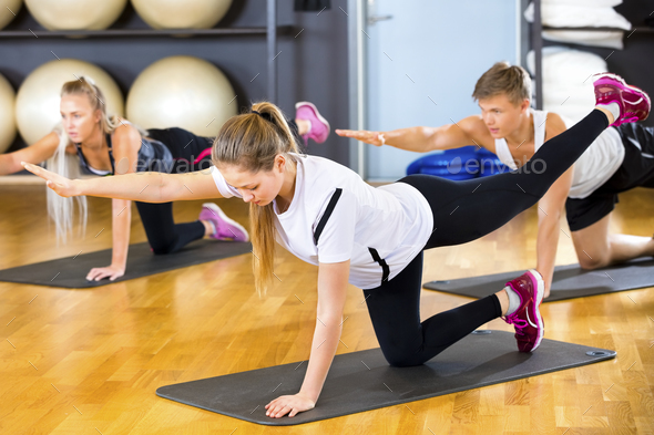 Woman In Sportswear Exercising With Friends On Mats - Stock Photo - Images