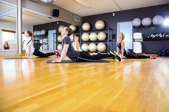 Group exercising body flexibility and balance at fitness gym - Stock Photo - Images