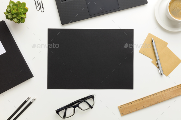 Top view of modern white office desk with black paper in center - Stock Photo - Images