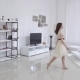 Beautiful Young Woman with Bare Feet and a Beige Dress Moves in the Interior in the Living Room  - VideoHive Item for Sale