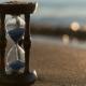 Hourglass on the Beach Sand Beach. Daylight Saving Time Concept