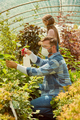 People fertilizing plants in greenhouse - PhotoDune Item for Sale