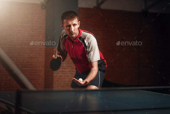 Man with racket in action, playing table tennis - Stock Photo - Images