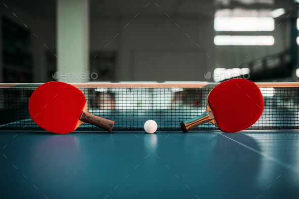 Two tennis rackets and ball against net on table - Stock Photo - Images