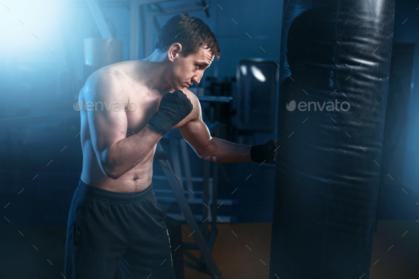 Man in black handwraps exercises with bag in gym - Stock Photo - Images