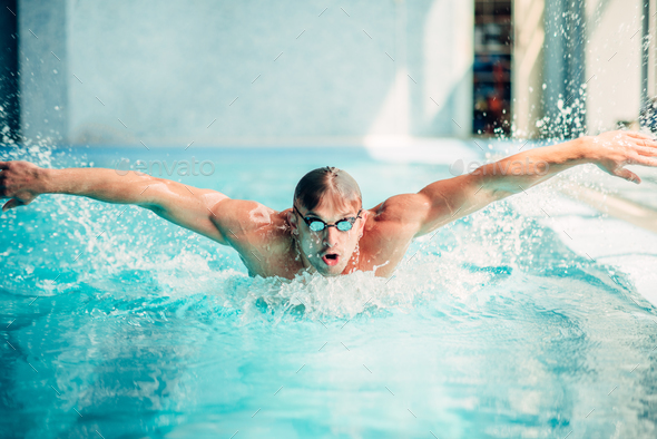 Athletic swimmer swims in butterfly style - Stock Photo - Images