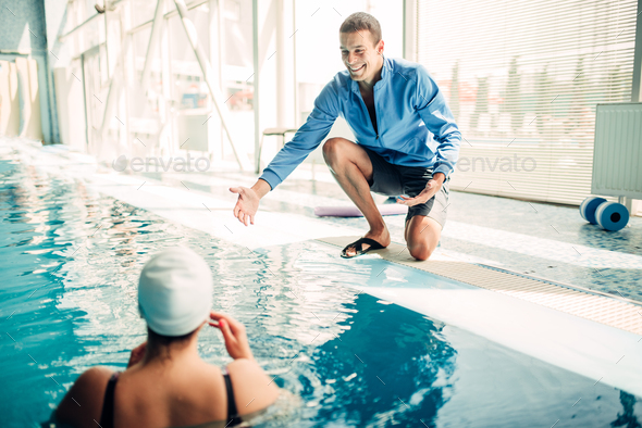 Female swimmer in cap with male personal trainer - Stock Photo - Images
