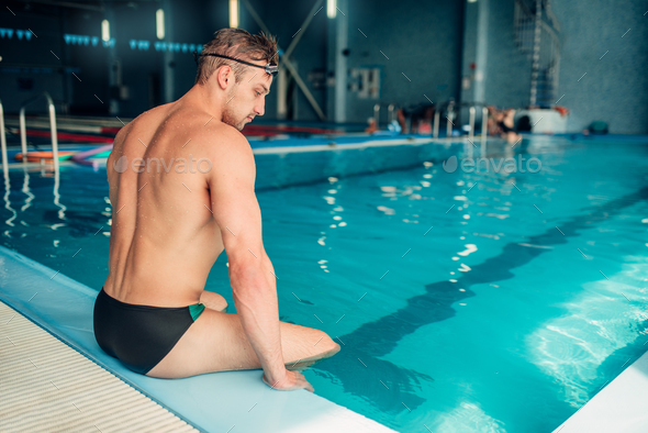 Athletic male swimmer sits on the curb, back view - Stock Photo - Images