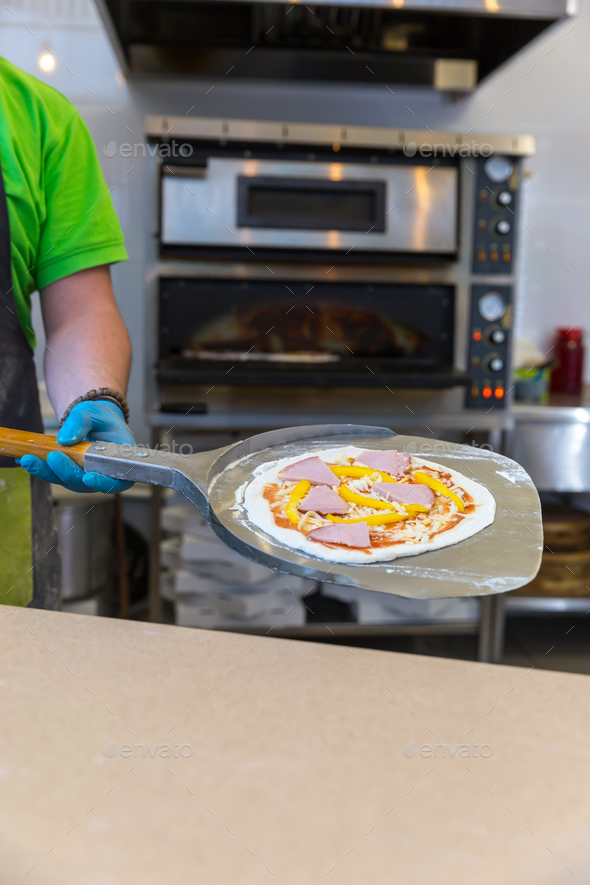 Baker hands with shovel, cooking pizza - Stock Photo - Images
