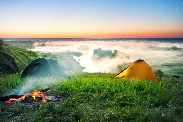Tent camping on hill over misty river - Stock Photo - Images