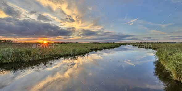 Sunset over river in  marshland nature reserve - Stock Photo - Images