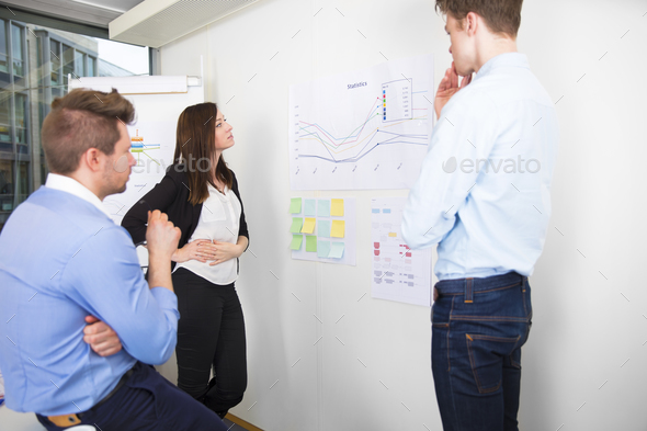 Business Professionals Discussing Over Line Graph In Office - Stock Photo - Images