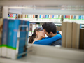 Young Adults College Students Kissing In Library