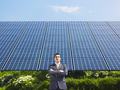 Business Man Standing Proud Against Wall Of Solar Panels