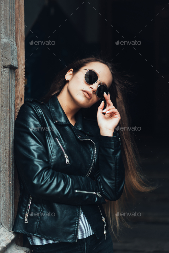 Beautiful girl in a black jacket and sunglasses - Stock Photo - Images