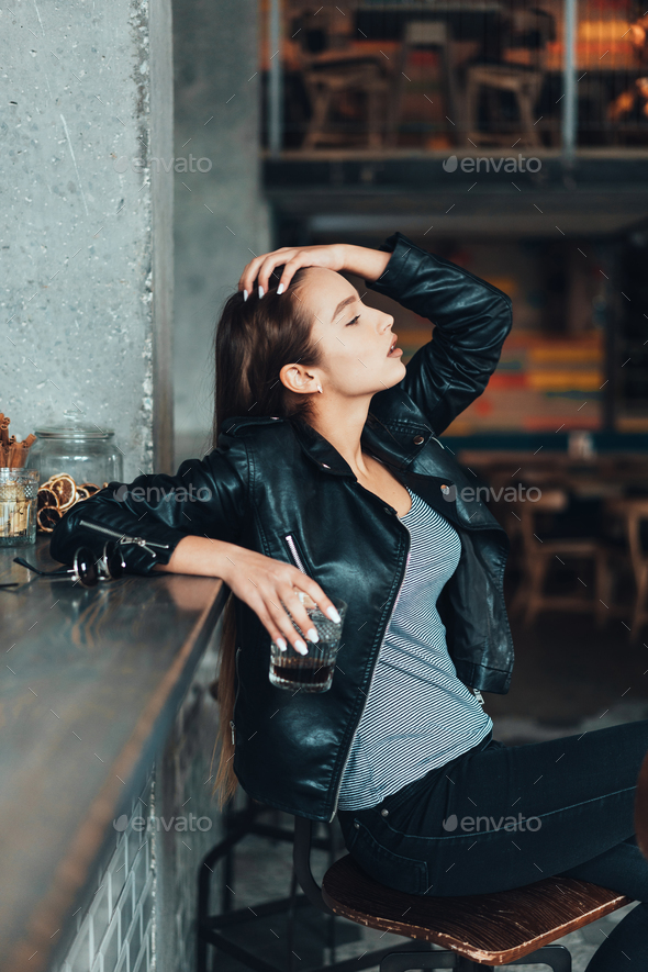 Beautiful girl in a black jacket in a cafe - Stock Photo - Images