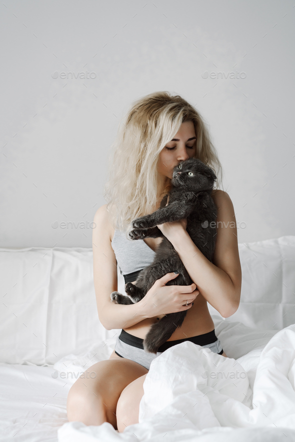 Happy young woman hugging a cat - Stock Photo - Images