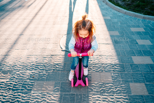 Little girl with blonde hair rides on scooter - Stock Photo - Images