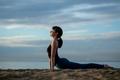 Yoga asana outdoors on beach. up facing dog pose