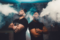 Two men vaping in an authentic room with brick walls