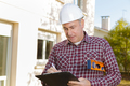 architect with clipboard in hardhat at construction site