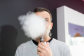 man obscured behind a cloud of vaporizer smoke