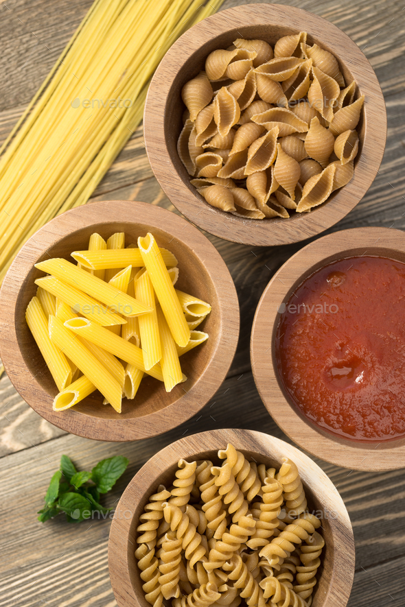 Variety of Pasta Wooden Bowls Cutting Boards Marinara Sauce - Stock Photo - Images