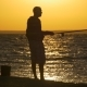 Man Fishing in Sea with Shining Water at Sunset - VideoHive Item for Sale