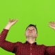Man Raises His Arms Up and Holds Something. Green Screen
