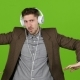 Man Listens To Music Through Headphones, Dances and Builds Grimaces. Green Screen