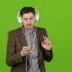Guy Listens To Music Through Headphones, Dances and Sings. Green Screen