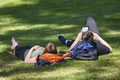 Young couple resting and reading on the park. Leisure time