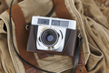 Vintage camera with backpack on the ground. Travel background