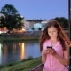 Pretty Young Girl Using Smartphone Near the Railing on Waterfront in Evening Time, Old City, River - VideoHive Item for Sale