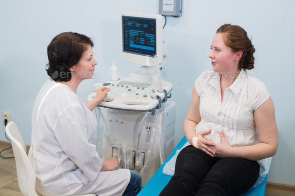 Satisfied pregnant woman having doctor's appointment with ultrasound diagnostics - Stock Photo - Images