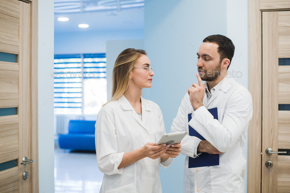 Two doctors discussing diagnosis while walking - Stock Photo - Images