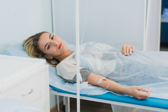 Pensive woman transfused lying in hospital ward - Stock Photo - Images