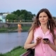 Pretty Young Girl Using Smartphone with Earphones Near the Railing on Waterfront in Evening Time - VideoHive Item for Sale