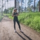 Girl Checking Time and Pulse on Pathway in Summer Forest