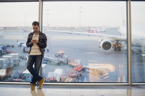 Traveler inside airport terminal. Young man using mobile phone and waiting for his flight. - Stock Photo - Images