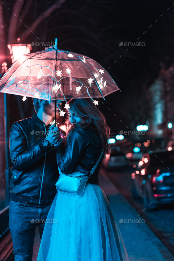 Guy and girl kissing under an umbrella - Stock Photo - Images