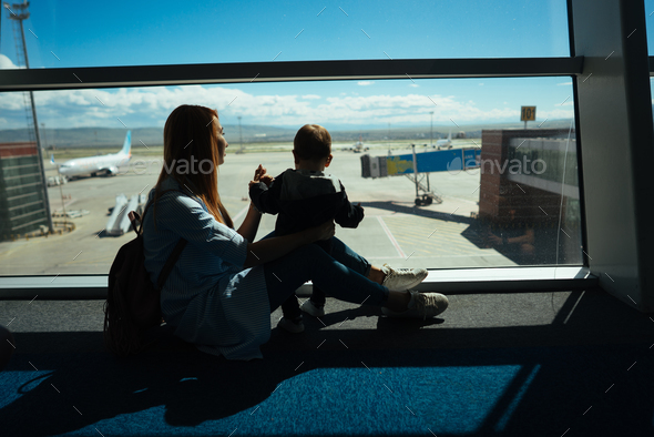Little boy and his mother sitting in an airport - Stock Photo - Images