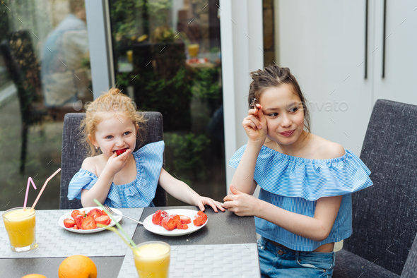 Two sisters drink juice in the kitchen - Stock Photo - Images