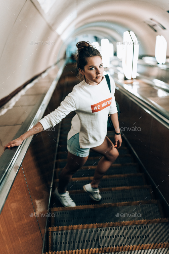 Beautiful young girl on escalator - Stock Photo - Images