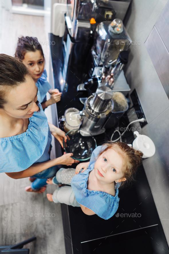 Happy family makes orange juice for breakfast - Stock Photo - Images