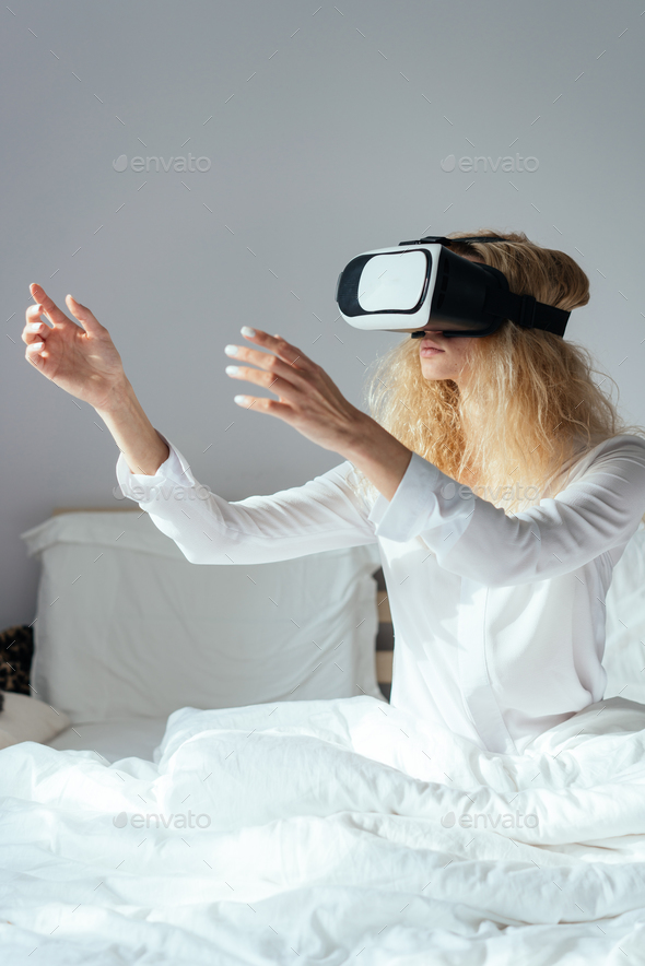 Girl sitting on a bed with VR headset - Stock Photo - Images