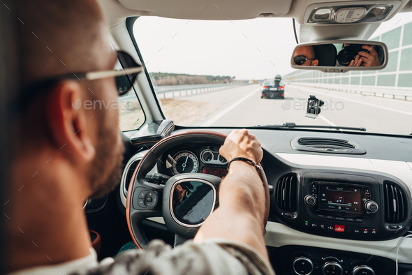 The man in the car traveling on the road - Stock Photo - Images