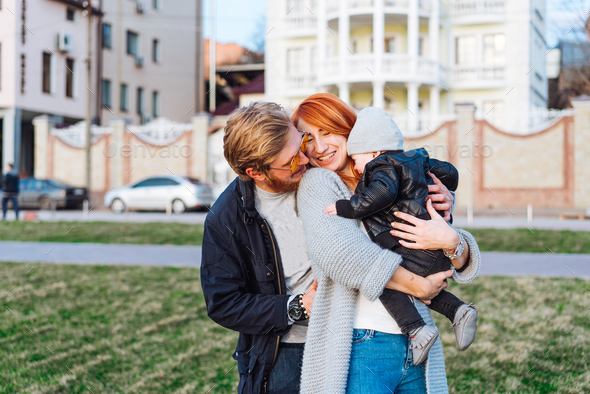 happy mom dad and son hugging in the park - Stock Photo - Images