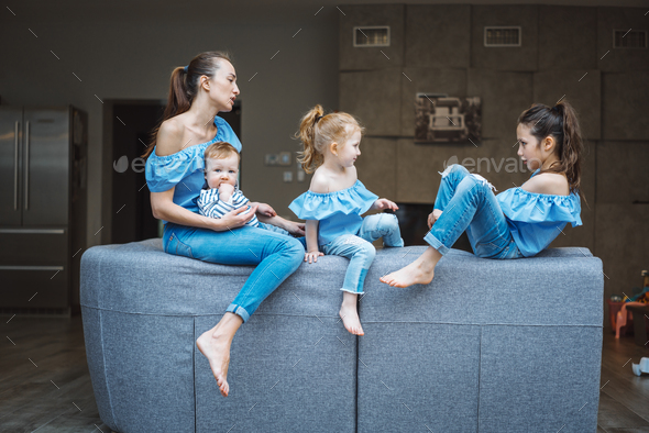 Mom, two daughters and a little son on the couch - Stock Photo - Images